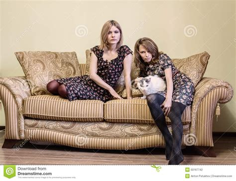 two girls having on the couch two beautiful girls in dresses sitting on a sofa stock