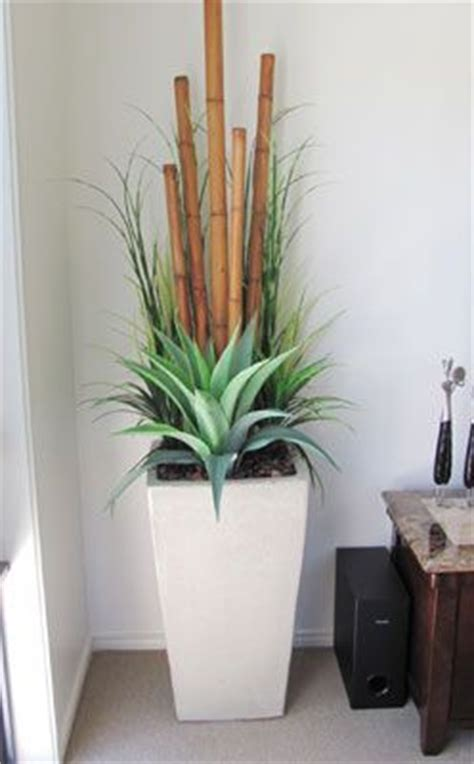 decorative bamboo canes in a wood grain planter artificial bamboo love this idea large planter bamboo poles agave and grass