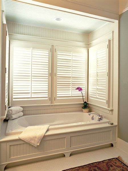 bathtub surround with window window blinds hung over a bathtub window apt second