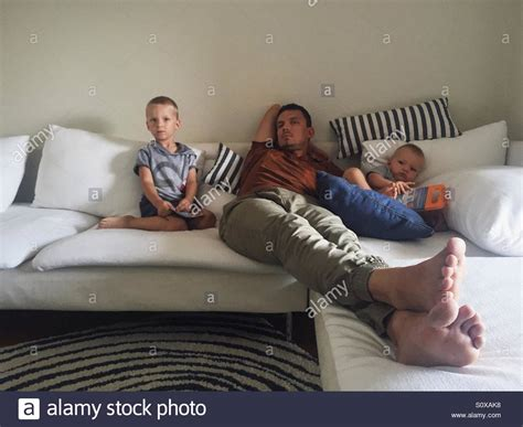 kids on couch dad and kids relaxing on the couch stock photo royalty