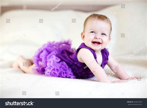 how to dress baby for bed laughing baby girl in purple dress on white bed stock