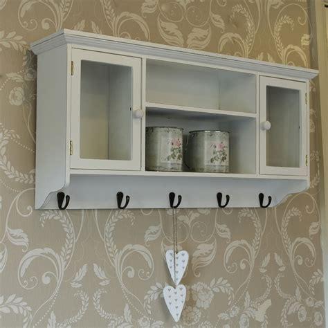 White storage shelf with cupboard and towel key hooks wall