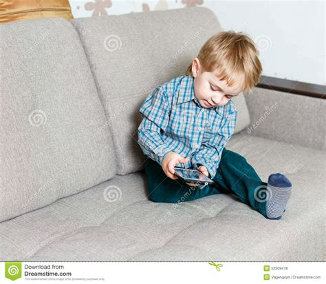 boy on couch boy sitting on a sofa with a smartphone stock photo