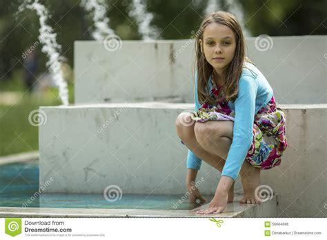 cute teenagers cute girlie plays near the city fountain walking stock
