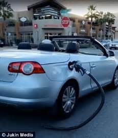 man oblivious   gas pump nozzle hanging  car daily mail