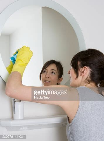 how to clean mirrors in bathroom woman cleaning bathroom mirror rear view stock photo