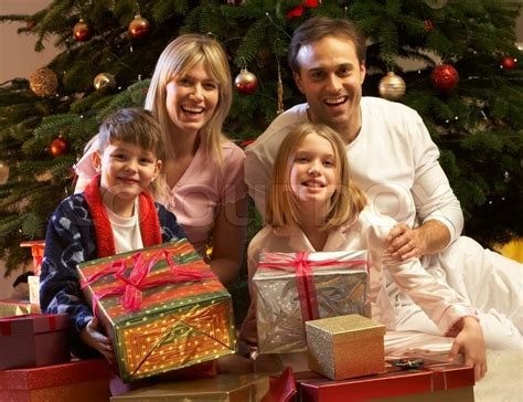 Family Opening Christmas Present In Front Of Tree   Stock ... Happy Kids Opening Christmas Presents