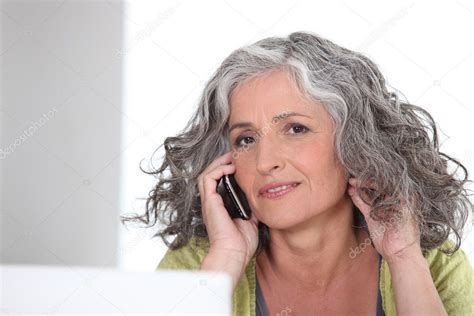 show me pictures of 63 year old women attractive older woman with a phone stock photo