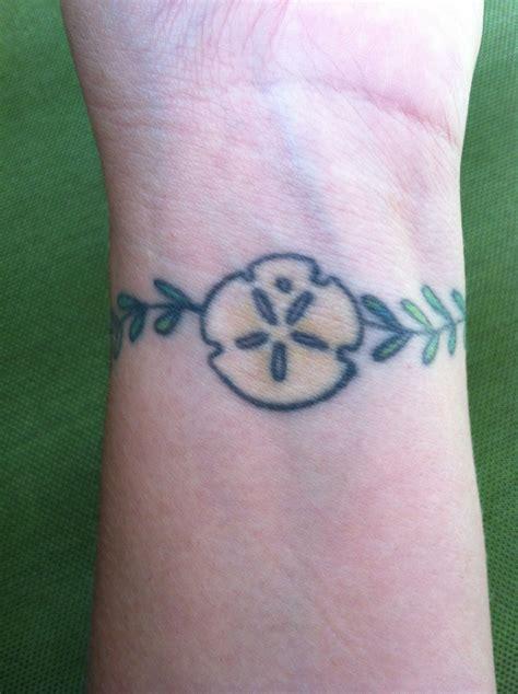 personal tattoo design wrist tat of sand dollar w seaweed that wraps around