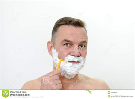 what percentage of middle age men shave their pubic hair man shaving his beard with a razor and lather stock photo