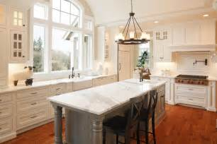 Ceiling height window affords natural light in this white kitchen