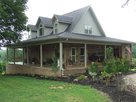 wrap around porches dormered farmhouse with green metal roof and wrap around
