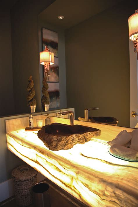 bahtroom fresh flower decor beside round sink under tiny led light shines through a white onyx countertop