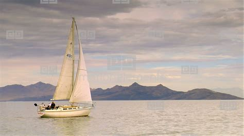 sailboat in water a sailboat glides on calm water near mountains stock video