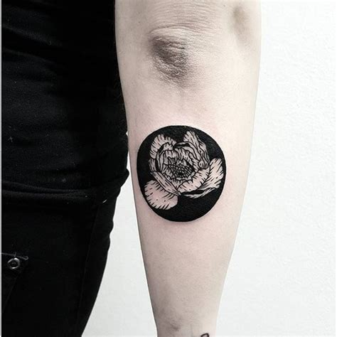 black circle tattoo circle shaped black ink forearm of small flower