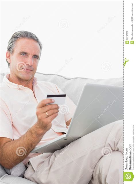 br casting couch man on his couch using laptop for shopping online smiling