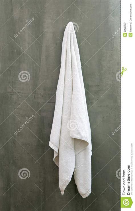 drape towel hanging white towel draped on exposive concrete wall stock