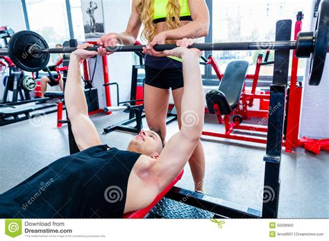 better bench press woman with personal trainer at bench press in gym stock