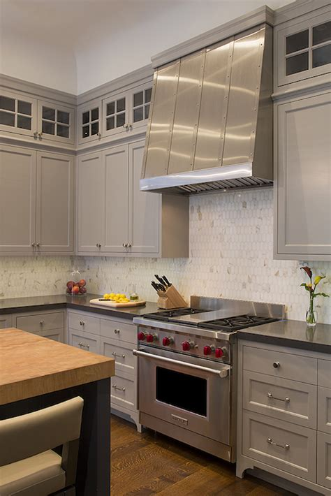 small white kitchen with steel hood oval marble backsplash transitional kitchen artistic