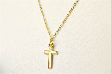 gold cross necklace small gold cross pendant on a gold by
