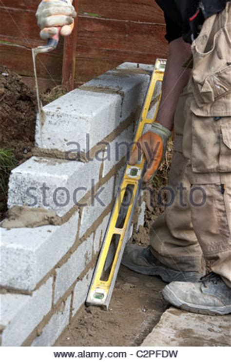 bricklaying wall with half cement blocks building a