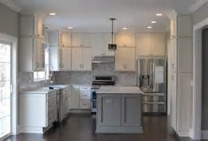 kitchen has white shaker cabinets the perimeter gray marble style island