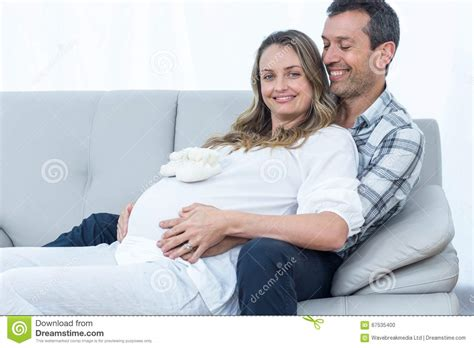pregnancy couch pregnant couple sitting on sofa stock photo image 67535400