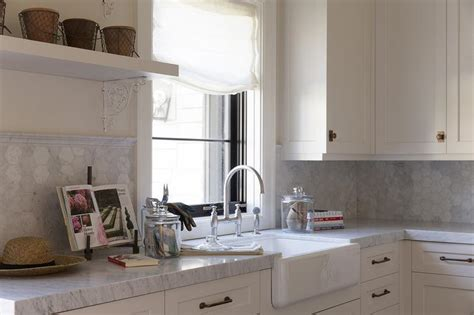 white laundry room cabinets with antique brass hardware