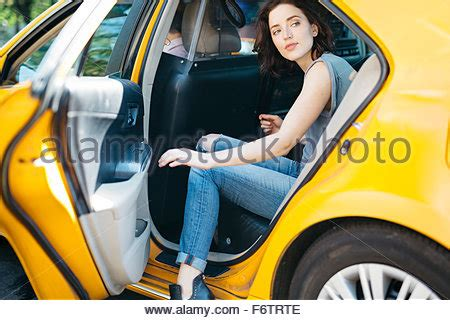 a woman gets a new getting into yellow taxi new york us stock photo