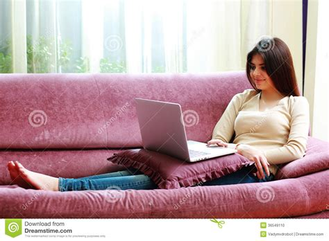 lying on a sofa young beautiful smiling woman lying on the sofa with