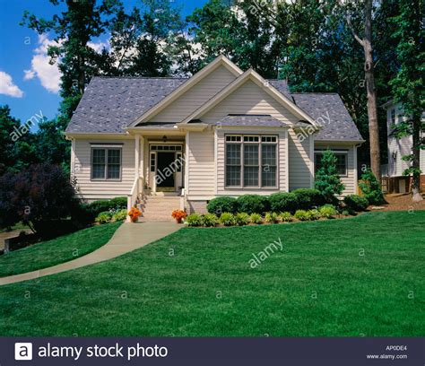 small cream colored house with a large yard and small