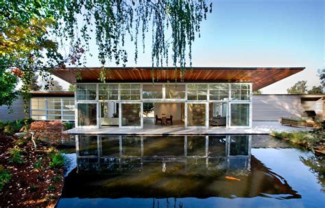 sustainable homes sustainable home wraps around man made pond and lush