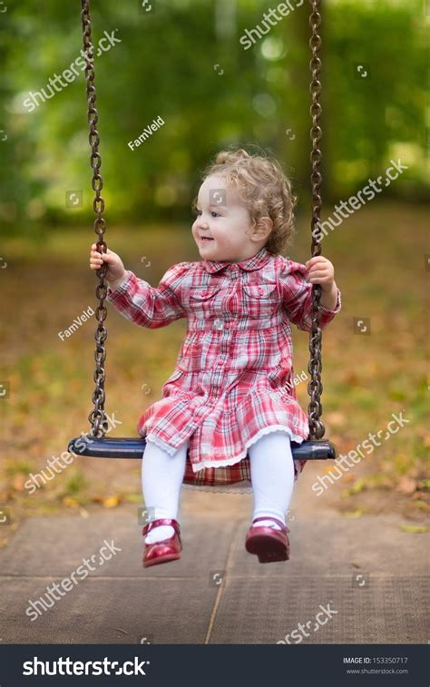 baby on a swing adorable baby girl beautiful curly hair stock photo