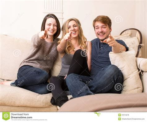 two girls having on the couch group of happy teenagers on a sofa pointing stock photo