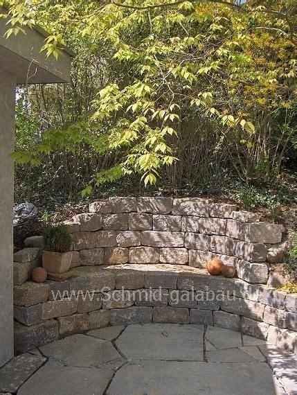 sitzplatz im garten mit steinmauer und brunnen