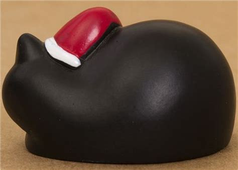 cute black lying cat with red santa claus hat from japan