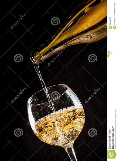 versamento in vino bianco di versamento in un bicchiere di vino