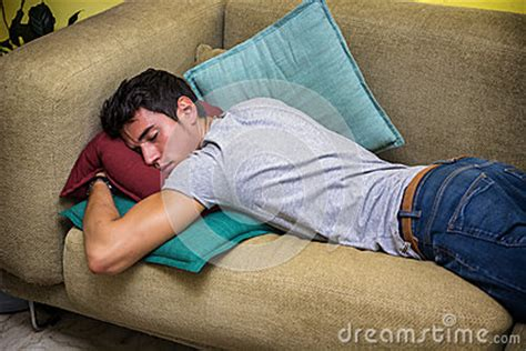 sleeping on the couch depression drunk young man sleeping on the living room couch stock