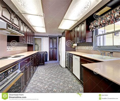 Old Wood Narrow Kitchen With Carpet And Curtains. Stock