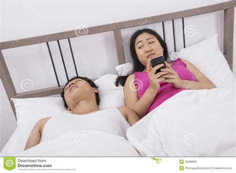 man using cell phone in bed stock images image 33817024 woman using cell phone while looking at man sleeping in