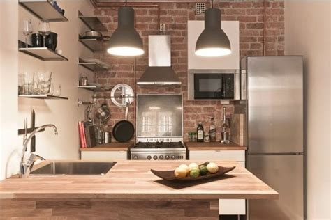 tiny but trendy open space apartment featuring exposed brick kitchen walls