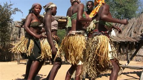 hd stock video footage two women flaunt tradition and african art face carving in wood rain in background