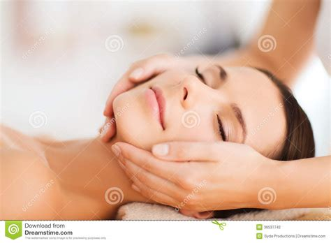 comforting hands massage beautiful woman in spa salon having facial stock