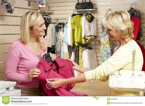 sales assistant with customer in clothing store stock image image 10971857