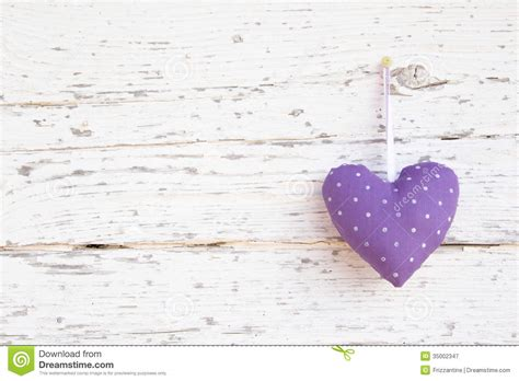 romantic dotted heart shape hanging above white wooden
