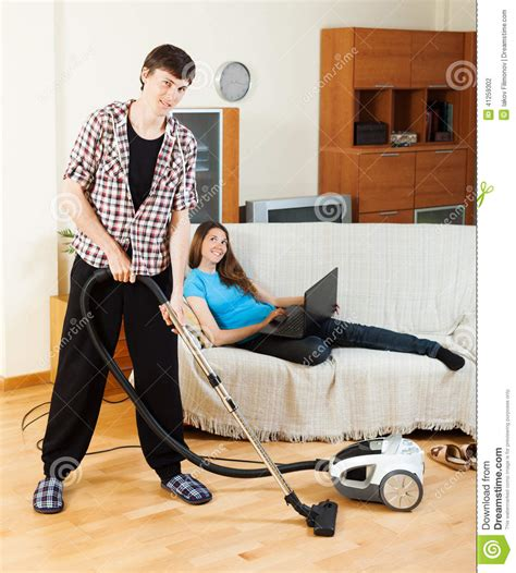 cleaning couches at home man doing house cleaning during girl resting stock photo
