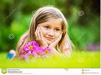 Portrait Of A Smiling Little Girl Lying On Green Grass Royalty Free