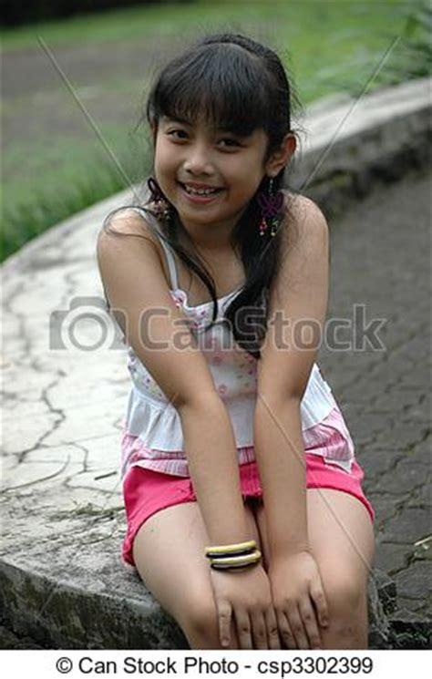 Tiny Pretender Model Japanese | stock photographs of little girl sit down in park little