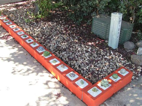 painted cinder block landscaping border with succulents