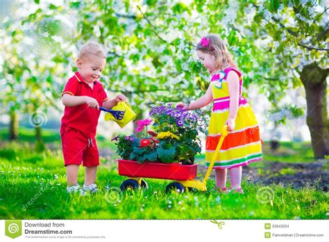 Gardening With Toddlers In A Garden With Blooming Cherry Trees Stock Photo